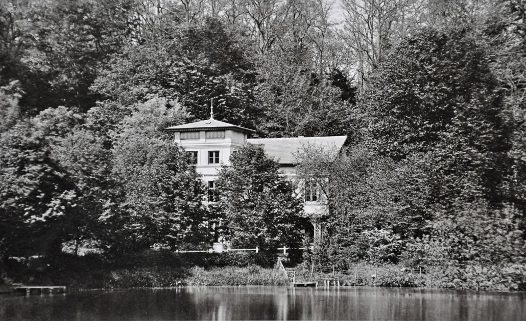 Auf der Schwarz-Weiß-Fotografie ist im Vordergrund der Friedrichsruher Schlossteich zu sehen und dahinter das sogenannte Turmhaus.