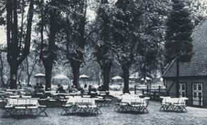 Zu sehen sind zahlreiche Tische, die unter Bäumen stehen. Einige sind mit Gästen besetzt.