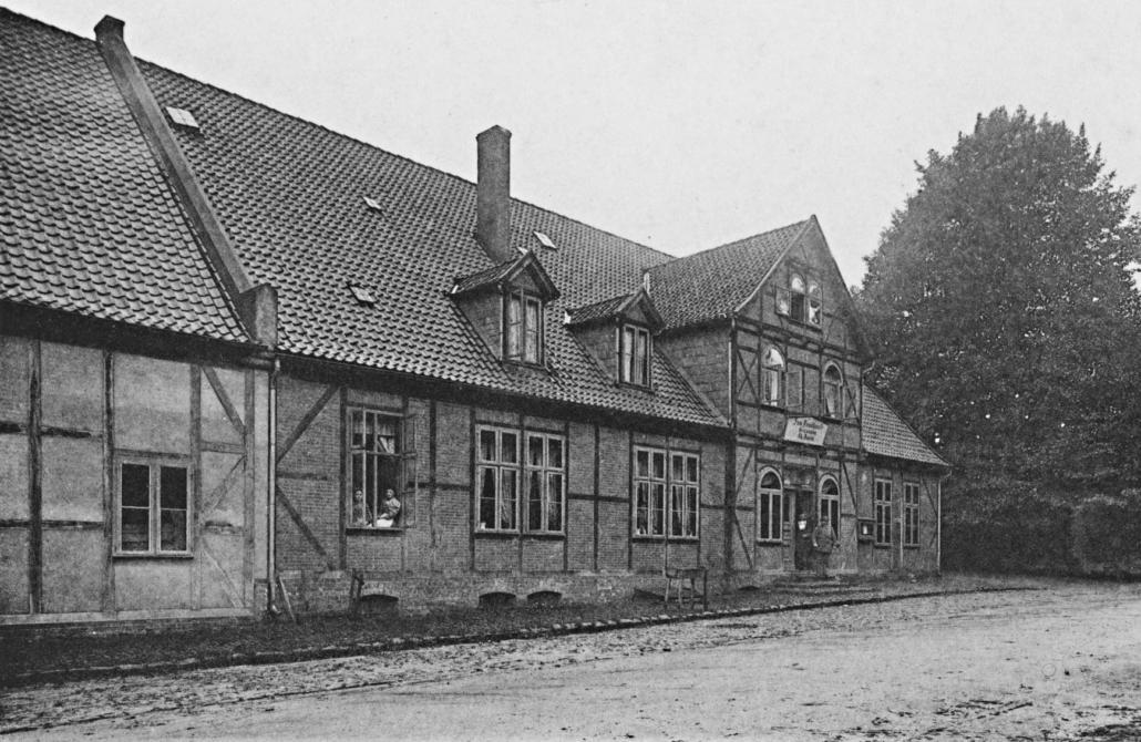 Auf der Schwarz-weiß-Fotografie ist ein Fachwerkhaus zu sehen. Im Eingang stehen zwei Männer, an einem offenen Fenster sitzen zwei Frauen.