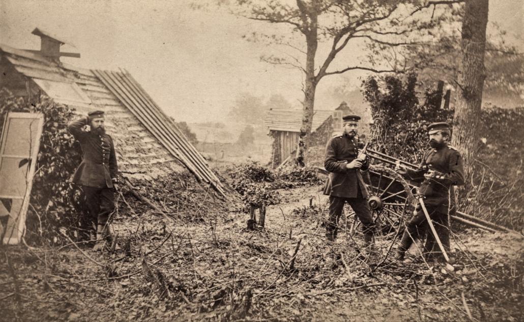Drei Männer in Uniformen stehen auf einer Flächen, aus der Wurzeln ragen, in der näheren Umgebung stehen ärmliche Häuser.