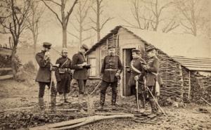 Secchs Soldaten stehen vor einer kleinen Hütten, die provisorisch aus Zweigen gebaut wurde.