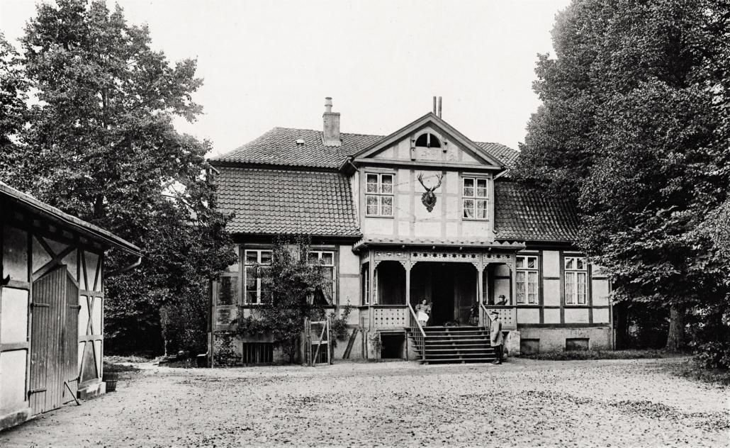 Zu sehen ist ein Fachwerkhaus mit Vortreppe und Veranda. Auf der Veranda sitzen zwei Frauen, vor der Treppe steht der Förster.